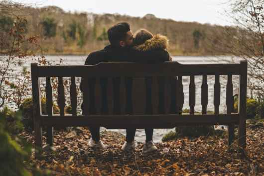 photo of couple sitting on bench